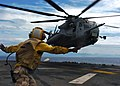 US Navy 061028-N-5067K-013 USS Essex (LHD 2) landing signal enlisted (LSE), Aviation Boatswain's Mate Airman Sendy Jolicoeur, guides in a CH-53E Super Stallion loaded with Marines and equipment assigned to Marine Medium Helicop.jpg