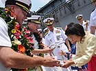 Senior US and Korean naval officers offer gifts while the carrier is in port.
