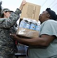 US Navy 080903-N-6266K-028 Army National Guard Spc. Jacquelyn Smith hands out bottles of water and boxes of meals ready to eat.jpg
