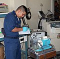 US Navy 090410-F-7885G-001 Petty Officer 1st Class Alvin Yabut, biomedicine repair technician aboard the Military Sealift Command hospital ship USNS Comfort (T-AH 20), inspects equipment at the general hospital in Port-au-Princ.jpg