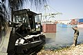US Navy 100125-N-1134L-089 Service members working with U.S. Marine Corps 8th Engineer Support Battalion use a bulldozer to remove submerged container boxes.jpg