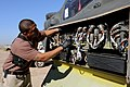 US Navy 100415-F-5214M-005 Petty Officer 2nd Class Lavonderick Campbell, a Navy customs administrator, inspects behind a front panel of an AH-64 Apache helicopter at Joint Base Balad, Iraq.jpg