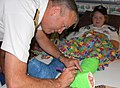 US Navy 100914-N-3038C-016 Rear Adm. William D. French autographs a patient's cast at Shriner's Hospital during a Caps For Kids event during Salt L.jpg