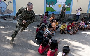US Navy 111215-N-PB383-274 Sgt. Marcos Bustos plays with children during a community service event at the Help the Cambodian Children Goodwill Cent.jpg