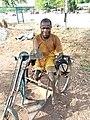 Un Cultivateur handicape', tenant sa daba en route pour le champ.jpg