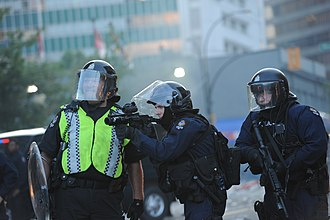 Non-lethal weapon - Vancouver Police Department officers in anti-riot gear and armed with tear gas grenade launchers confront Stanley Cup rioters.