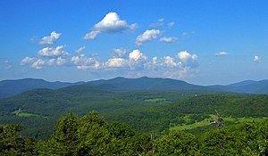 A range of mountains, mostly rounded and covered with green woods, seen past fields in the distance. Above them is a blue sky filled with little fluffy clouds.