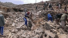 Villagers scour rubble for belongings scattered during the bombing of Hajar Aukaish - Yemen - in April 2015.jpg