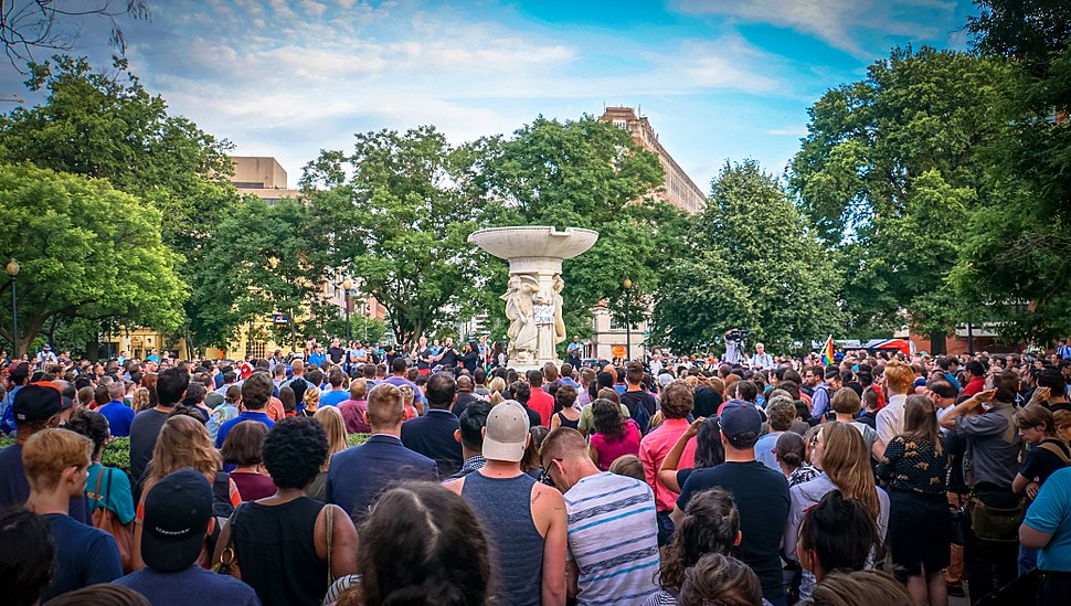 """Hundreds of people stand together listening to a man speaking from an outdoor stage. In the center of the crowd is a large statue with a paper sign affixed to it with tape; the sign reads: """"D.C. Loves You Orlando""""."""