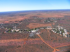 Aerial view of a small town surrounded by flat, red plains