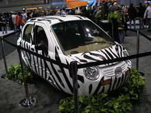 An extremely compact white car with black, zebra-like stripes behind black cordons