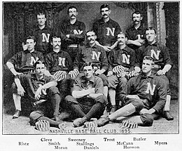 "A black and white photograph of twelve men arranged in three rows, standing, sitting in chairs, and sitting on the floor. They are wearing dark baseball uniforms with a white ""N"" on the chests."