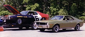 Shows two cars: Sunoco racing AMC Javelin on an open car hauling trailer and a 1970 Javelin SST finished in light green