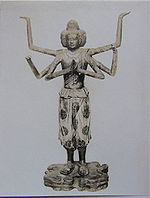 Front view of a standing statue with six arms and three faces. One pair of hands is joined in front of the body with the palms facing each other as if praying. A second set of arms is bend to the sides with the palms of the hands pointing upwards. Also the third pair of arms is bend somewhere between the positions of the other pairs of arms. The three faces point to the front and both sides of the statue. The statue is embellished with sculpted and painted wide three-quarter length trousers and sandals.