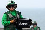 A Sailor displays an aircraft's weight before launch.jpg