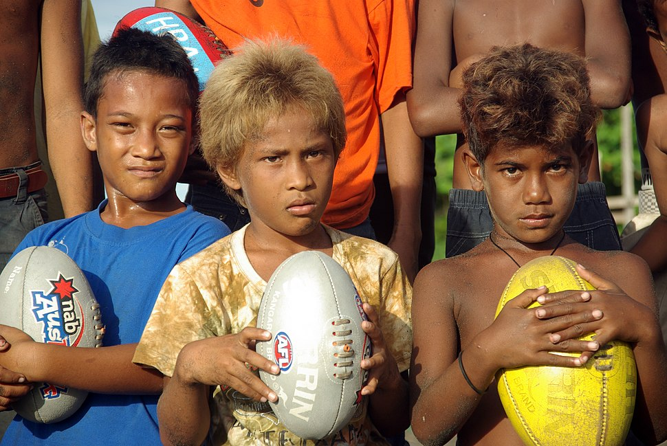 A close up shot of three junior AFL player holding footballs at the Lord Howe Settlement, Honiara. (10661462334)