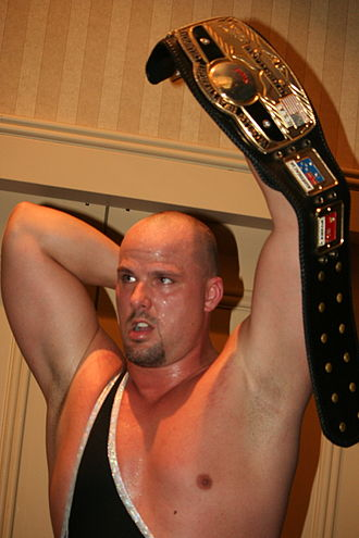 NWA World Heavyweight Championship - The belt used to represent the NWA World Heavyweight Championship (established 1948) recognized by the National Wrestling Alliance (being held aloft by five-time champion Adam Pearce). The flag of Australia and Canadian Red Ensign can be seen on the belt's strap
