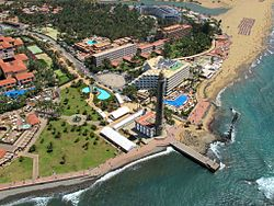 Aerial view of Maspalomas showing a cluster of hotel complexes, the lighthouse, beaches and sea