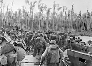 Black and white photo of a group of men wearing military uniform disembarking from boats and walking towards palm trees