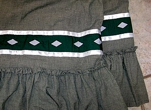 Stomp dance - detail of a stompdance skirt made by Ardina Moore (Osage-Quapaw), featuring rattlesnake-patterned ribbon work