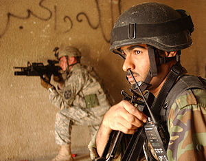 "An Iraqi and American soldier conducting a raid in Baghdad. The graffiti on the wall reads ""God is great"" in Arabic."