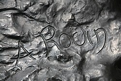 Artist's signature is raised above the surface of a sculpture.