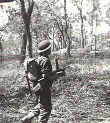 A soldier advances through the bush with a submachine-gun during training