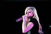 Avril Lavigne wearing a black gown and sining in to a microphone.
