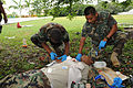 Belize Defence Force combat medic Lance Cpl. Leon Lopez, left, administers an intravenous solution into a volunteer casualty, center, with assistance from Cpl. Paul Shal, right, during a medical exchange 100830-A-CL600-076.jpg