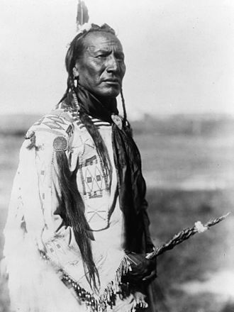 Hierochloe odorata - Blackfoot man holding sweetgrass braid