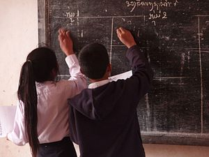 Pupils writing on the blackboard in a village ...