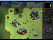 On the right is a small vertical panel witch icons and a small map. The remaining three quarters of the screen is a digital depiction of grass plain, with black and grey areas to represent unexplored regions. Three metallic looking buildings are placed on the plain, surrounded by military vehicles and personel. Certain units have gauges above them, representing their state of damage.