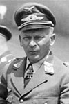 The head and shoulders of a man, shown in semi-profile. He wears a peaked cap and a military uniform with an Eagle above his right breast pocket, and an Iron Cross displayed at the front of his white shirt collar.