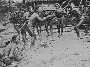 Mentawai people - A group of Mentawai men portraying chicken in a dance, circa 1900–1940.