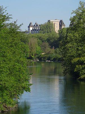 Photographie en couleurs d'un cours d'eau aux rives boisées; château en surplomb en arrière-plan.