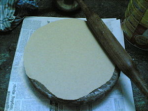 Rolling pin - A wooden belan rolling pin is used on a round chakla to make chapatis
