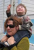A child with Down syndrome piggy-backing on an adult