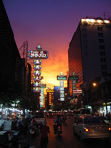 A street during sunset lined with many stalls and shops with a lot of signs bearing Thai and Chinese names