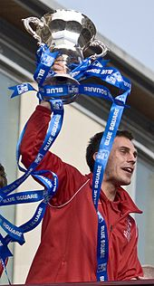 A man with dark hair is wearing a red jacket. He is holding aloft a trophy.