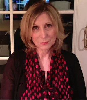 A low-quality photo of Christina Hoff Sommers, sitting in what appears to be her home, wearing a dark red shirt and red and black scarf.