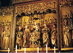 The central section of an elaborately carved, painted and gilded altarpiece showing the Virgin Mary and Christ Child seated in majesty and surrounded by saints and angels. Although the flesh and some details are painted in colour, most of the surfaces are gilt. The figures are all chubby-faced and have a charming quality.