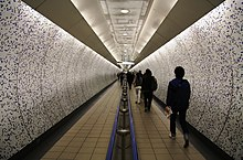 A view along a passage with curved walls covered in mosaic tiling and a semi-circular ceiling