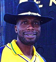 A black man in a wide-brimmed hat, wearing a yellow shirt