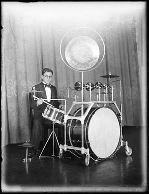 "Drum kit - Dance band drummer Stan Farmer in 1935 at Mark Foy's Empress Ballroom in Sydney, New South Wales, using a kit with bass drum pedal and a ""low sock"""