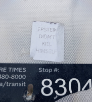 "A simple white sticker reading, ""Epstein Didn't Kill Himself."""