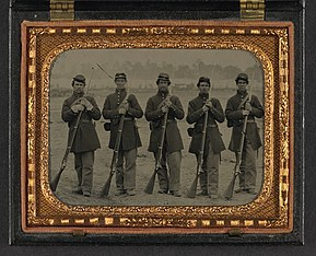 A sepia toned photograph of five soldiers standing at parade rest in a neat line