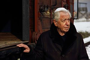 Frank Lowy - Lowy at the 2013 March of the Living in Auschwitz-Birkenau in front of the cattle car donated in memory of his father, Hugo.