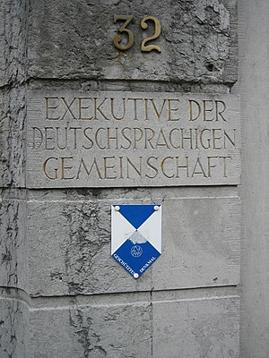 "Kulturdenkmal - Pillar outside the Council of the German Speaking Community of Belgium, which is housed in a Kulturdenkmal, marked with the emblem of the Hague Convention of 1954 with text ""Geschütztes Denkmal"", used to mark protected buildings and other structures in the German Speaking Community of Belgium."