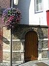 foto van Poort van de Latijnse school. Zandstenen poortje. Leeuwenmasker als sluitsteen. Opschrift op de rondboog: AMANDA PALLAS EXITU. Bijbehorend oude muur met natuurstenen lagen