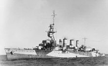 Black and white photograph of a World War II-era warship. The ship is painted in a camouflage pattern.